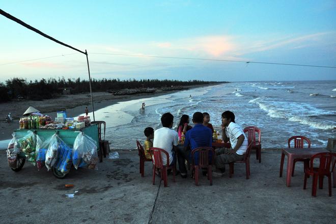 Bãi tắm thuộc xã Hải Đông vào buổi chiều tối. Không có cảnh hàng quán nối nhau dọc bờ, chỉ có một quán nước nhỏ trên đê phục vụ người dân trong xã ra tắm. Cát nơi đây rất mịn, bờ biển thoai thoải và sóng cũng vừa phải. Do không phát triển du lịch nên trong vùng rất hiếm nhà nghỉ, khách sạn. Tuy nhiên, việc nghỉ ngơi không đáng lo ngại, bởi chỉ cần đi quãng đường khoảng 10 km là tới thị trấn Quất Lâm hay khu du lịch Thịnh Long - nơi có rất nhiều khách sạn, giá phòng giao động khoảng 250 - 350 nghìn đồng/đêm.