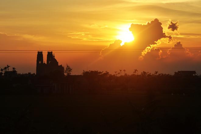 Ánh nắng hoàng hôn chiếu xuống những ngôi làng với tháp chuông nhà thờ nhô lên tuyệt đẹp.