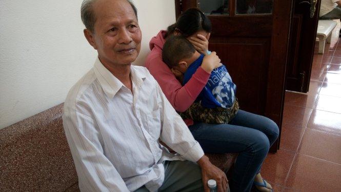 Cha ông Minh buồn rầu còn vợ, con ông Minh ôm nhau khóc tại sân tòa - Ảnh: Đức Tuyên