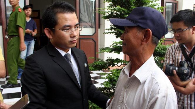 Luật sư Phạm Hoài Nam an ủi cha của bị cáo Minh sau khi tòa tuyên án - Ảnh: Đức Tuyên