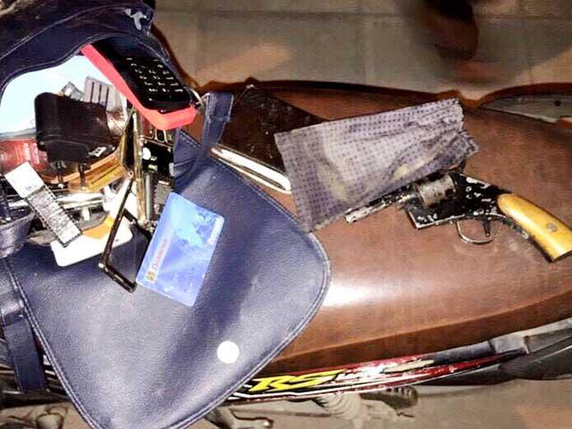 Chiếc túi xách nữ cùng nhiều điện thoại, thẻ ATM, và khẩu súng côn xoay.