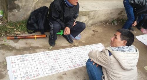 Những người đàn ông đang đăm chiêu trước nước cờ trong trò chơi cờ tướng. Ảnh: C. H