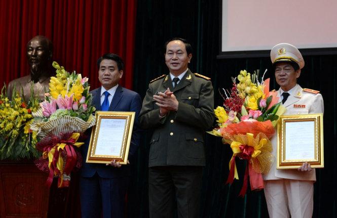 Bộ trưởng Bộ Công an Trần Đại Quang (giữa) tặng hoa chúc mừng Thiếu tướng Nguyễn Đức Chung (trái), Chủ tịch UBND thành phố Hà Nội, nguyên giám đốc Công an Hà Nội, Thiếu tướng Đoàn Duy Khương (phải), tân Giám đốc Công an HN - Ảnh: Xuân Thành
