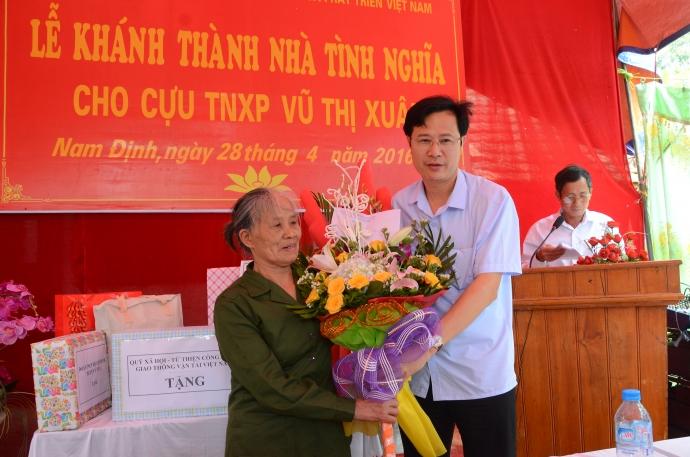 Ông Đinh Xuân Hùng, Phó giám đốc Sở GTVT Nam Định tặng quà và hoa cho cựu TNXP Vũ Thị Xuân
