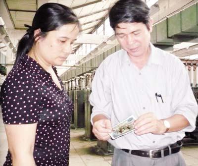 Ông Đặng đang cố gắng nhớ 3 phụ nữ được in hình lên tiền là công nhân nào. Ảnh: T.G