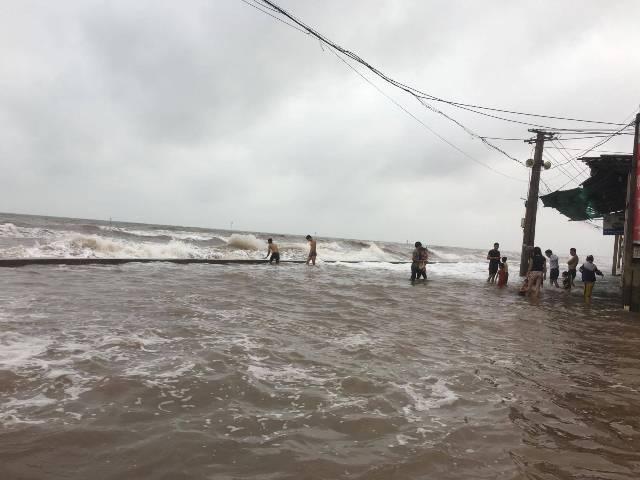 Đường ven biển ngập nước đã trở thành bãi tắm với người dân và du khách.
