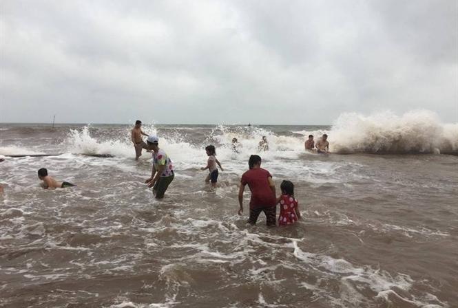 Nước biển ở Quất Lâm dâng cao nhưng người dân vẫn ra tắm.