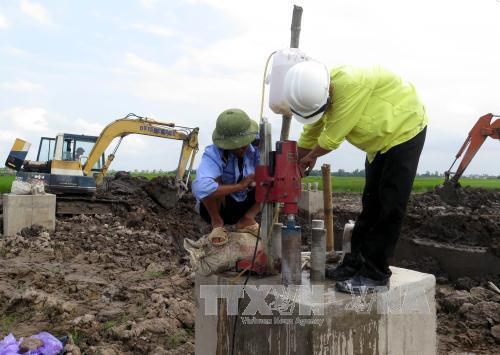 Đơn vị kiểm định chất lượng bê tông tiến hành khoan trụ bê tông cột điện cao thế để lấy mẫu kiểm định chất lượng. Ảnh: Văn Đạt-TTXVN