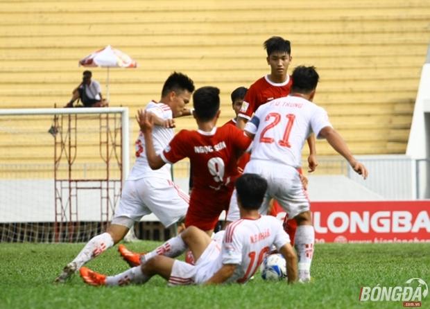 Cầu thủ Viettel (áo đỏ) sa lầy tại sân của đội chủ nhà Đồng Nai. Ảnh: Quang Thịnh.