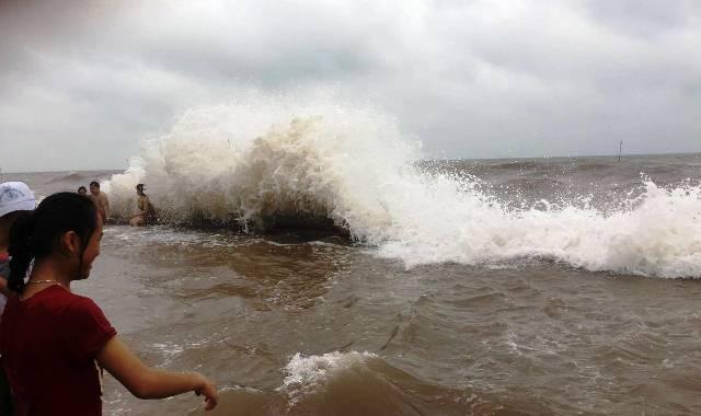 Những cơn sóng mạnh liên tiếp tấp vào bờ đê, ảnh hưởng đến việc lưu thông xe cộ và kinh doanh của các tiểu thương tại biển Quất Lâm