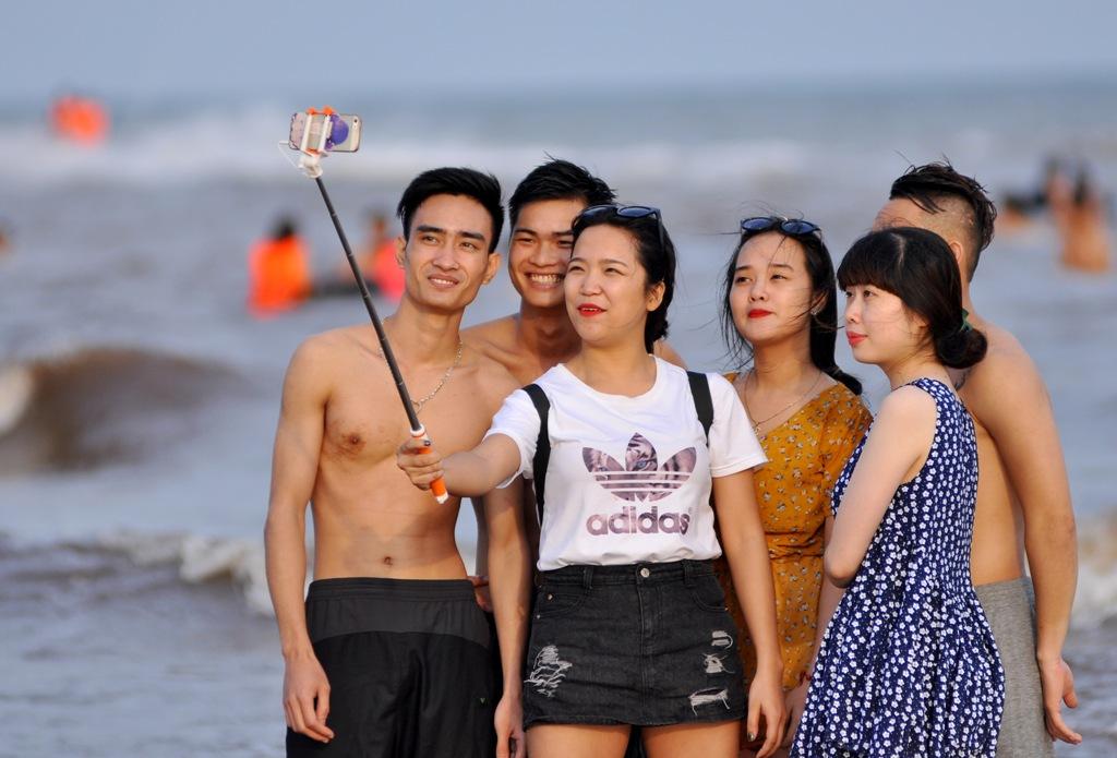 Nhiều nhóm khách du lịch còn thích thú lưu lại những bức ảnh tại bãi tắm Quất Lâm.