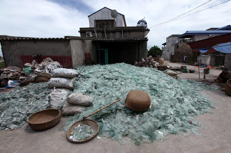 Mảnh kính vỡ được gia đình anh Phạm Ngọc Hân, chủ một lò thổi thủy tinh ở làng Xối Trì chất thành đống lớn giữa sân nhà
