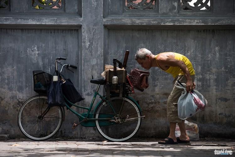 Ông Doãn, 72 tuổi cùng chiếc thùng đồ bán trà và chiếc xe đạp cũ. Ông bán trà cạnh nhà máy dệt Nam Định hơn 27 năm nay - Ảnh: NAM TRẦN
