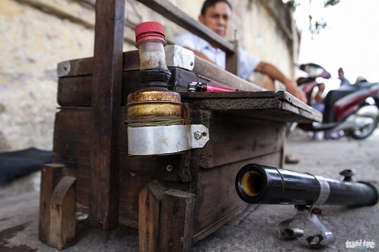 """Chiếc hòm như này có tuổi đời lên tới gần 30 năm. Nó được làm bằng gỗ có hai tầng, là vật để đựng những cốc, chén, những bao thuốc là, bật lửa đã trở thành """"kỷ vật"""" đặc biệt gắn liền với những người bán nước trà bên nhà máy dệt hay những người bán trà trên tàu lửa - Ảnh: NAM TRẦN"""
