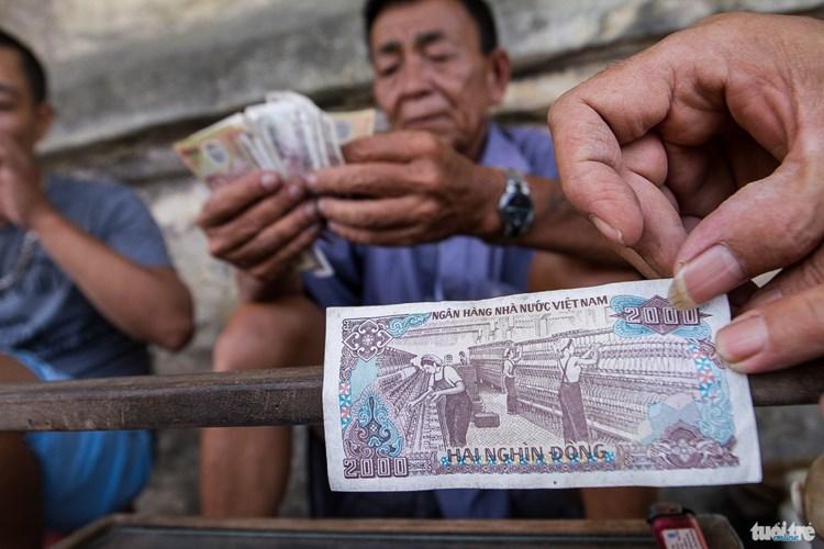 Nhà máy dệt hiện nay đang bị phá dỡ, hình ảnh trên đồng tiền hai ngàn đồng này cũng là một trong ký ức còn lại của những người bán và người uống trà nơi đây - Ảnh: NAM TRẦN