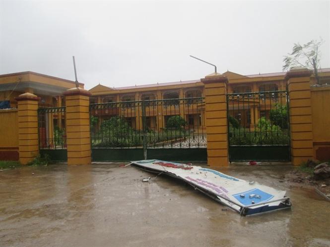 Biển quảng cáo của một Trường THCS bị gió thổi bay xuống đất .