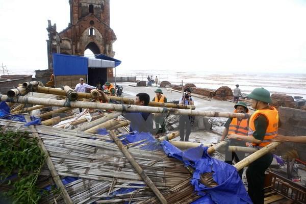 Cán bộ đồn Biên phòng Văn Lý giúp người dân khắc phục sau bão số 1 đi qua tại khu vực bãi biển xã Hải Lý (Hải Hậu). (Ảnh: Minh Quyết/TTXVN)