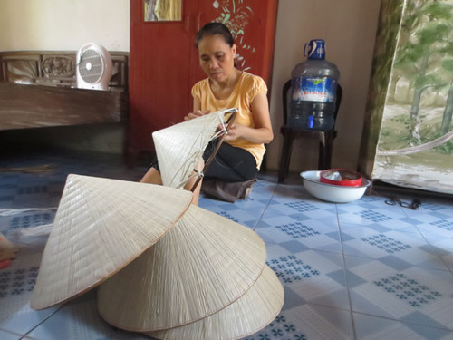 Bà Nguyễn Thị Hinh (ngụ thôn Đào Khê Hạ) làm nón lá bán cho khách du lịch đến thăm làng nghề làm nón - Ảnh: H.L