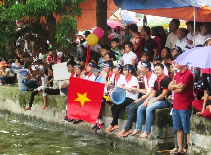 Những cổ động viên ngồi đông kín bên bờ sông để cổ vũ cho những đội thi.