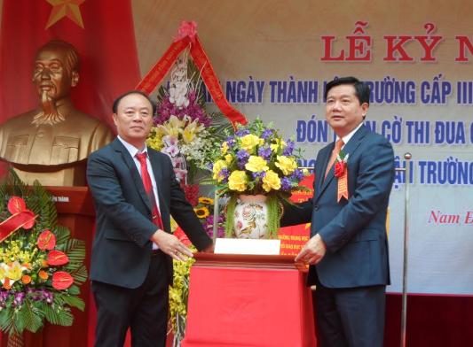 Ông Đinh La Thăng, Ủy viên Bộ Chính trị, Bí thư Thành ủy thành phố Hồ Chí Minh trao tặng Trường THPT Ngô Quyền lẵng hoa tươi thắm.