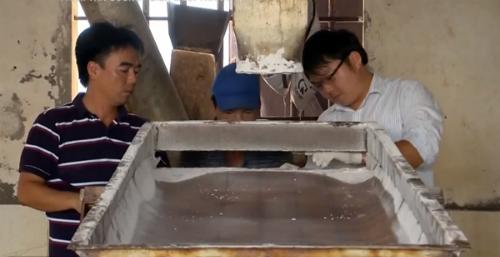 Anh Phạm Văn Cương cùng công nhân nhà máy bảo trì máy móc. Ảnh: VTV.