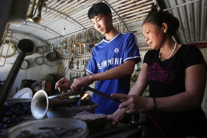 """Nguyễn Trung Kiên 19 tuổi (trái), tiếp xúc với nghề từ năm 10 tuổi. Cậu cho biết: """" Trong gia đình, các thành viên đều có thể làm hoàn thiện một chiếc kèn, ai cũng được học nghề từ nhỏ nên làm thành thạo""""."""