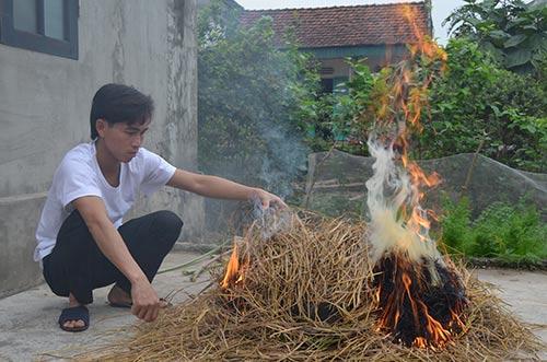 Sau khi phủ lên một lớp rơm, người dân bắt đầu đốt lửa nướng cá