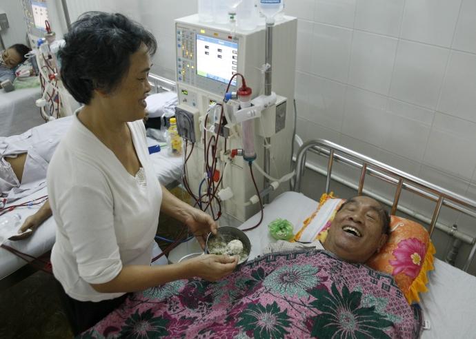 Bà Đậu chăm sóc chồng bên giường bệnh.