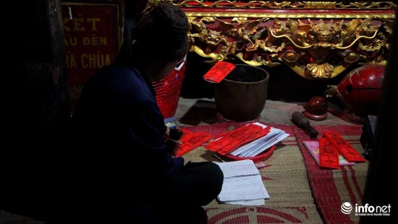 """Một thầy chùa đang ngồi xếp lại những """"lá sớ"""" (ghi tên tuổi, mong ước của người đến xin)."""