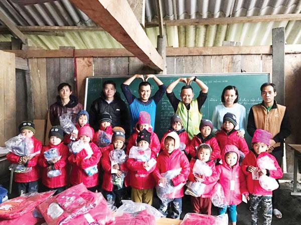Tổng giám đốc Phan Minh Chính (đứng thứ 3 từ phải sang) đích thân tặng quà cho các em học sinh điểm trường Nghều Lài (Cao Bằng) ngày 19-12.