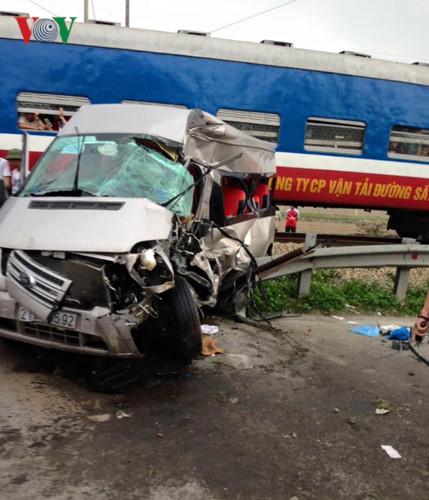Cú đâm khiến xe khách bị đẩy đi xa, nằm kẹp giữa đoàn tàu và hành lang an toàn đường sắt