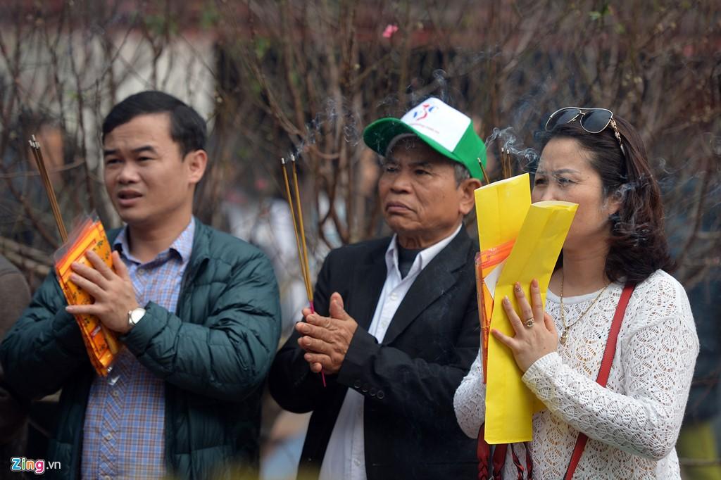 Bên ngoài sân, nhiều du khách đi theo đoàn đến tham quan và thắp hương.