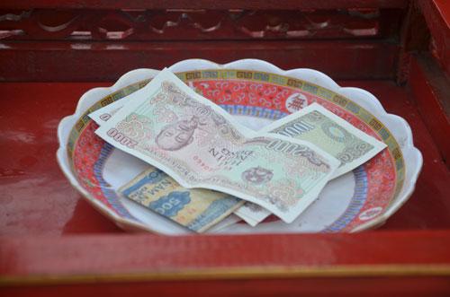 Tiền lẻ được bỏ vào đĩa đặt phía trong kiệu