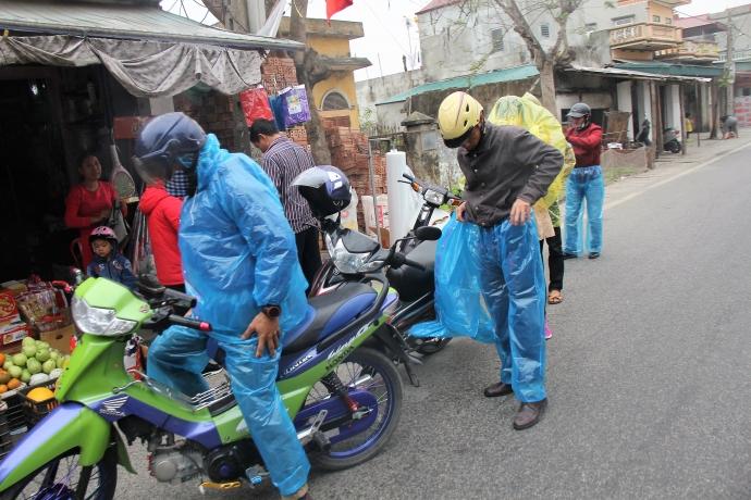 Nhiều người dân phải ghé hàng tạp hóa trên đường vào hội chợ Viềng để mua áo mưa tiếp tục hành trình