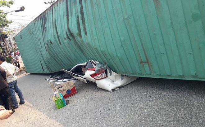 Sau khi bị thùng xe container đè trúng, chiếc ô tô con biến dạng hoàn toàn.