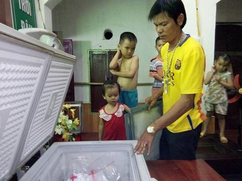 Anh Đỗ Quang Hà sắp đặt từng túi nilon bó hài nhi vào tủ đông lạnh