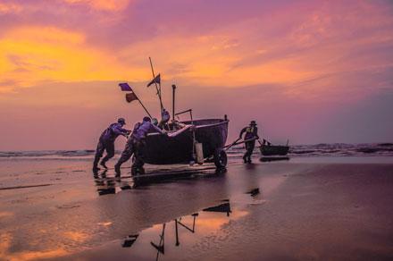 Rạng đông, những người ngư dân đã tập trung ở bờ biển để cùng nhau đẩy thuyền ra khơi.
