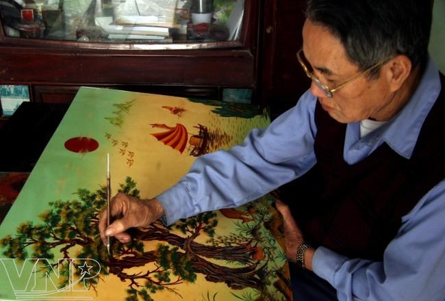 Nghệ nhân Đinh Khắc Tuyến (làng Cát Đằng) đang chỉnh sửa một bức tranh sơn mài.