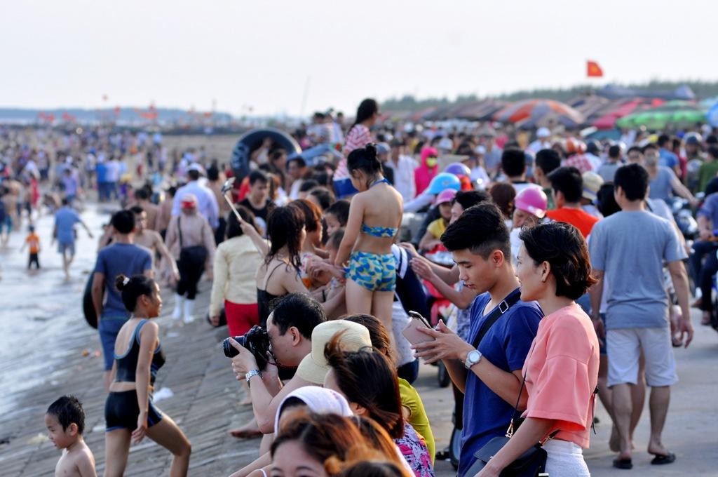 Ghi nhận của PV chiều ngày 30/4, dòng người đổ về bãi tắm Quất Lâm đông kín khu vực đường bờ đê.
