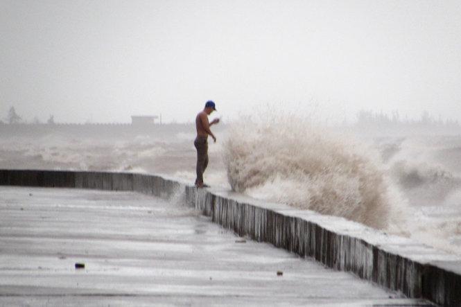 Chiều 27-7 tại vùng biển Quất Lâm, thị trấn Quất Lâm, huyện Giao Thủy, người dân bất chấp sóng lớn ra tại bãi biển ngóng tình hình cơn bão số 1