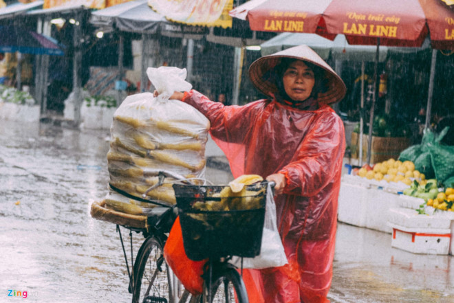 Người phụ nữ bán hàng rong dưới mưa. Ảnh: Việt Hùng.